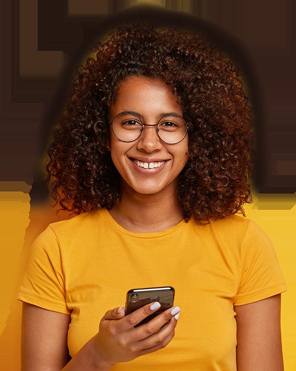 Jovem negra sorrindo segurando um celuar com uma camiseta amarela